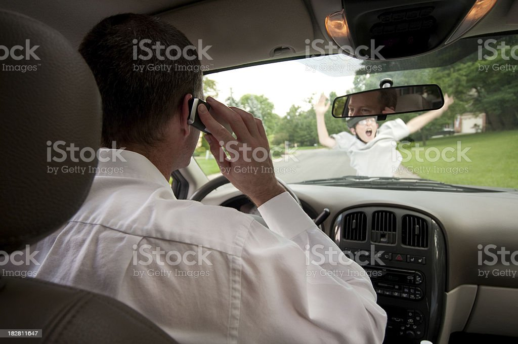 Man driving while talking cellphone doesn't see boy on skateboard royalty-free stock photo