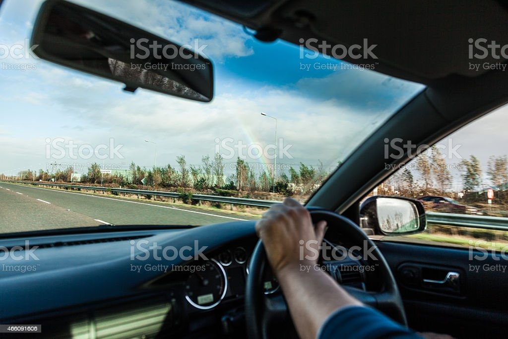 A man driving with his hands on the steering wheel stock photo
