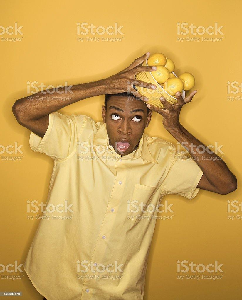 Man dropping bowl of lemons balancing on his head. royalty-free stock photo