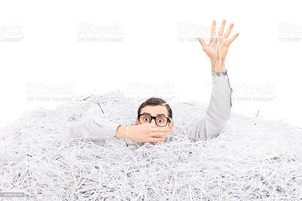 Man drowning in a pile of shredded paper stock photo