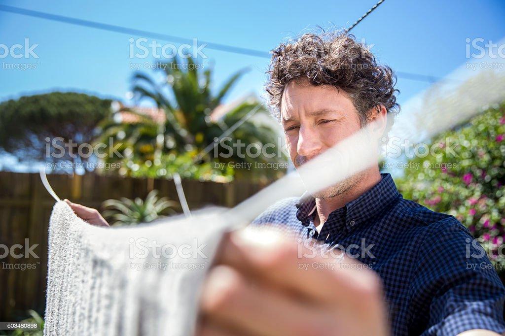 Man drying towel in yard stock photo