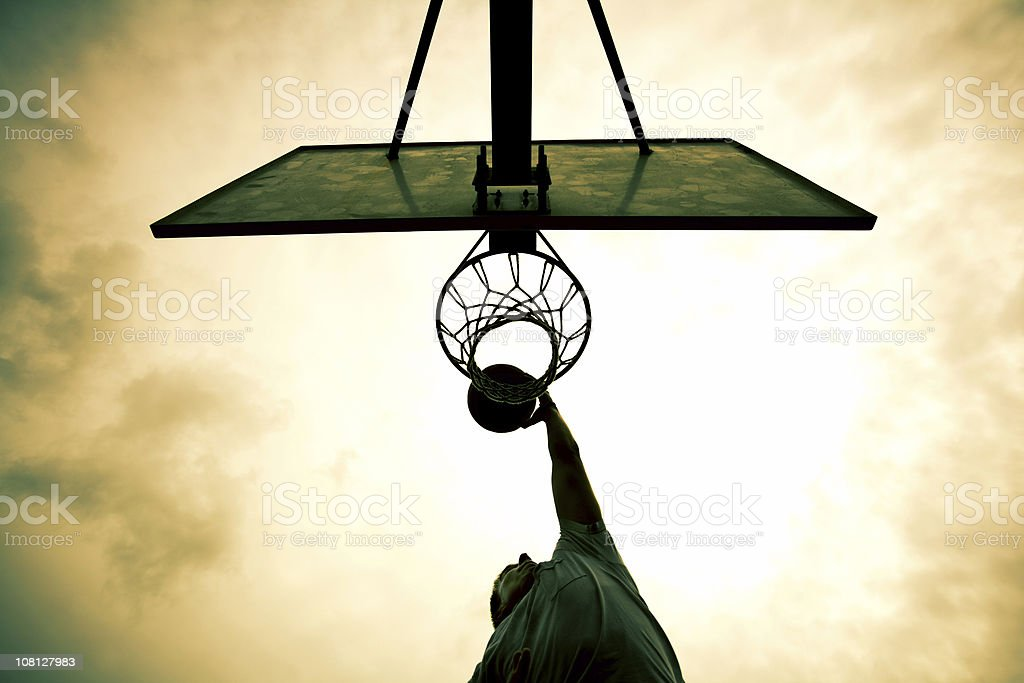 Man Dunking Basketball in Net stock photo