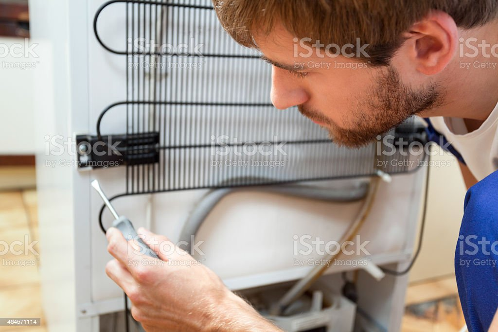 Man during fridge repair stock photo