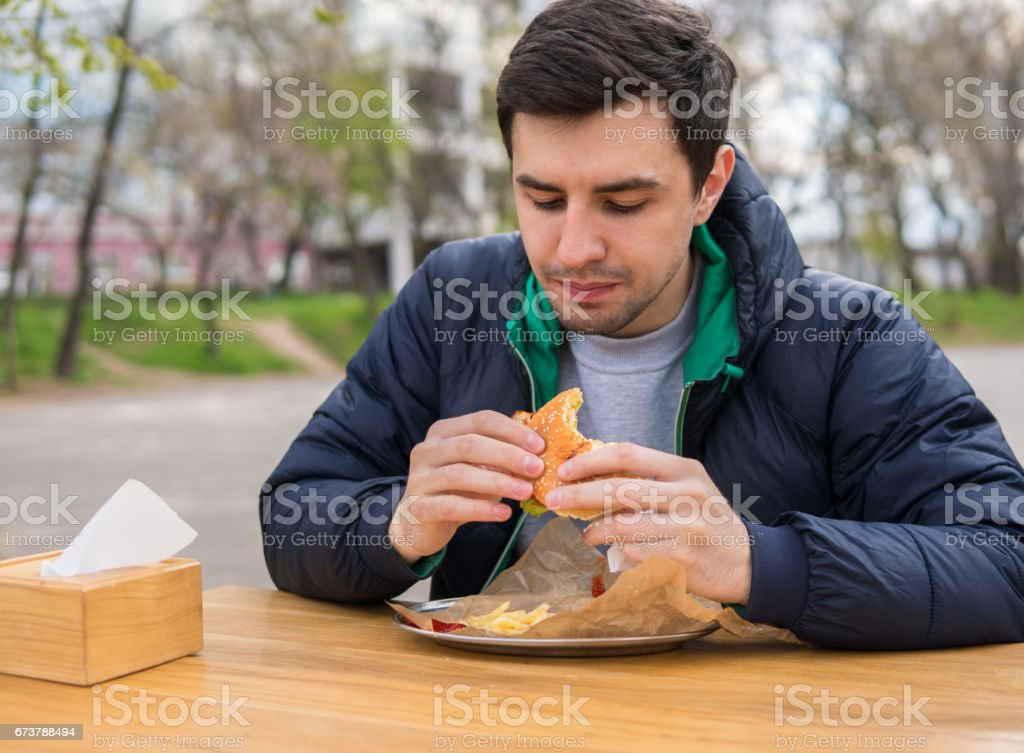 man eating a burger in street food cafe stock photo