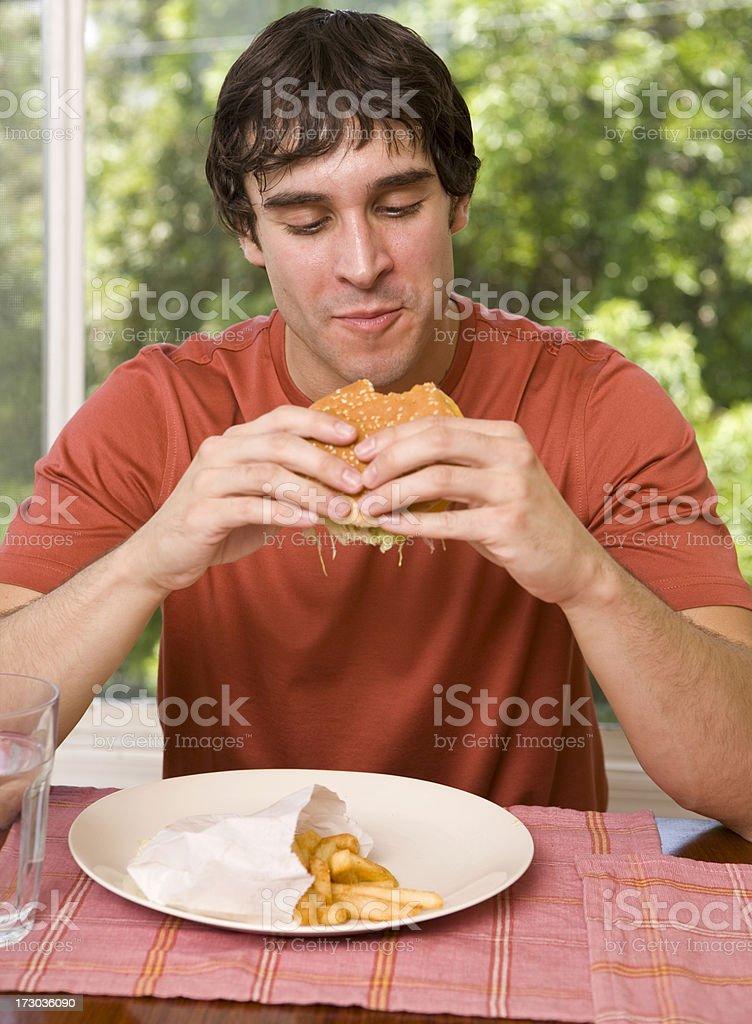 Man eating a hamburger and fries royalty-free stock photo