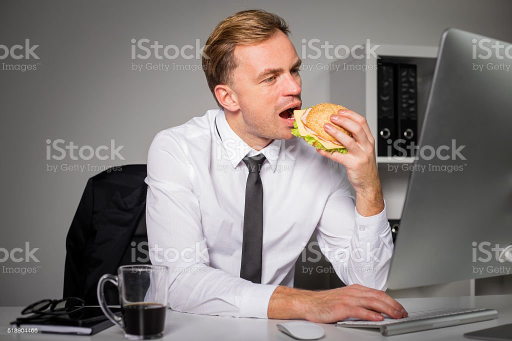 Man eating burger and working stock photo