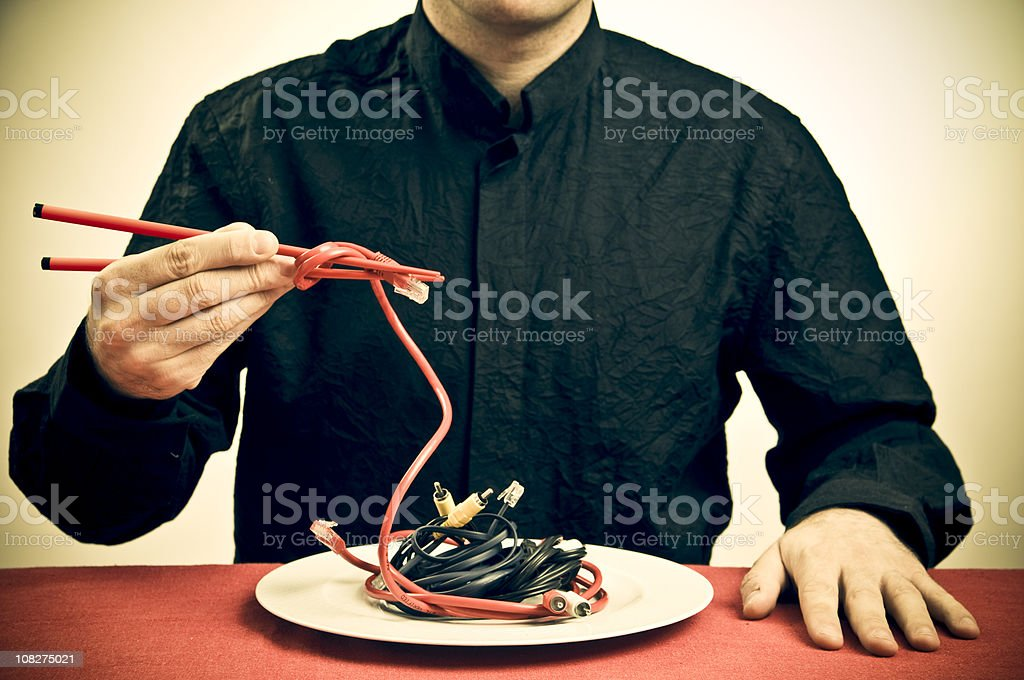 Man Eating Cables with Chopsticks, Toned stock photo