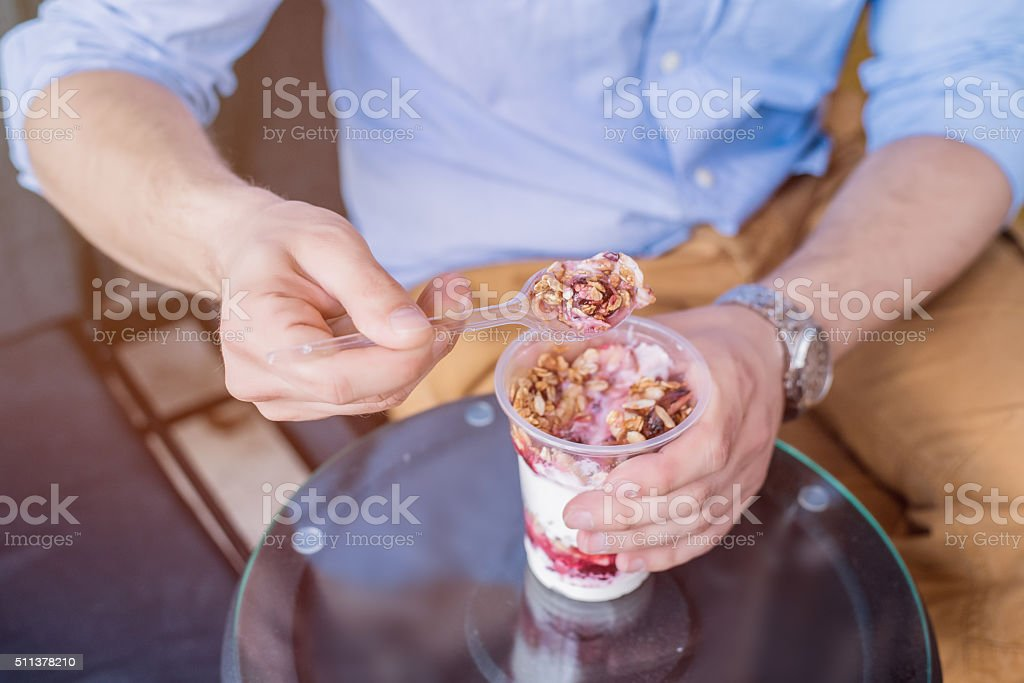 Man eating granola breakfast stock photo