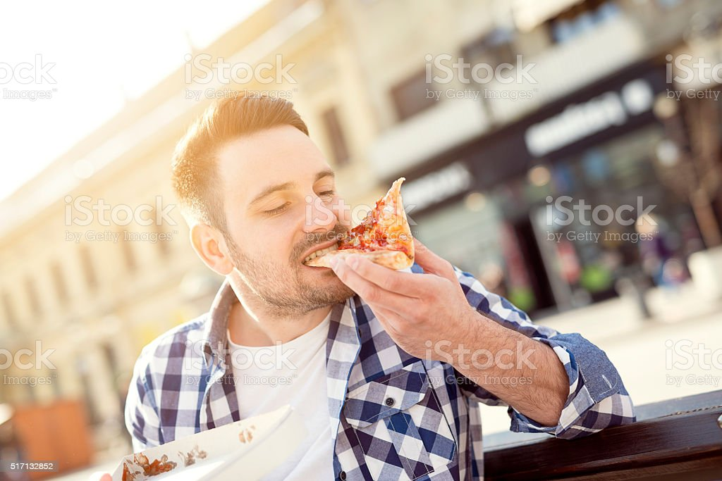Man eating pizza snack outdoors stock photo