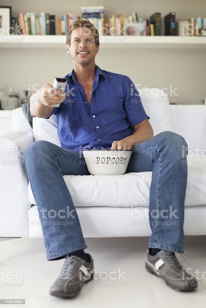 Man eating popcorn and watching TV stock photo