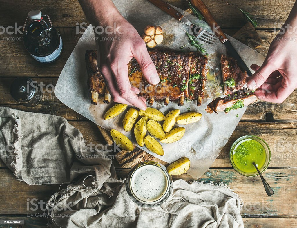 Man eating roasted pork ribs with garlic, rosemary, potato. sauce stock photo