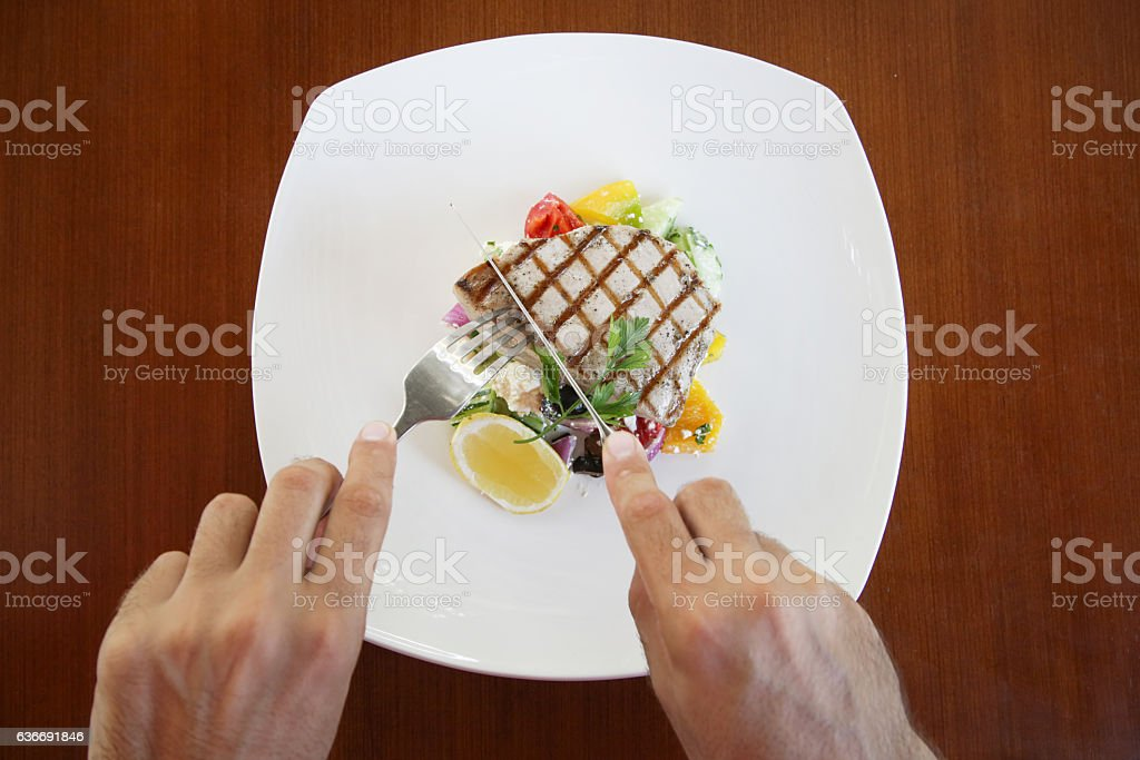 Man eating tuna steak - top view stock photo