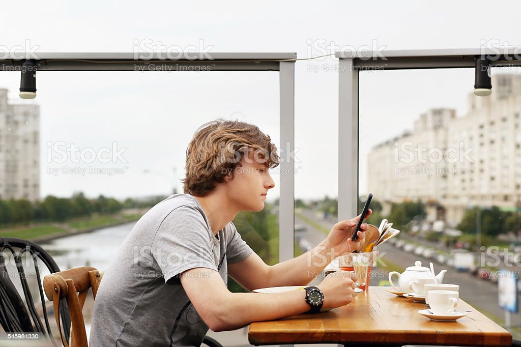 Man eating  while scrolling on phone stock photo