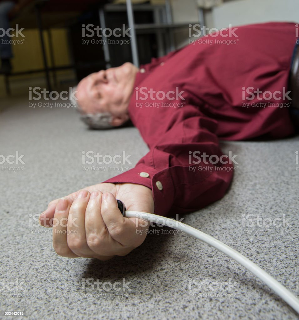 Man electrocuted, lying injured on a household floor stock photo