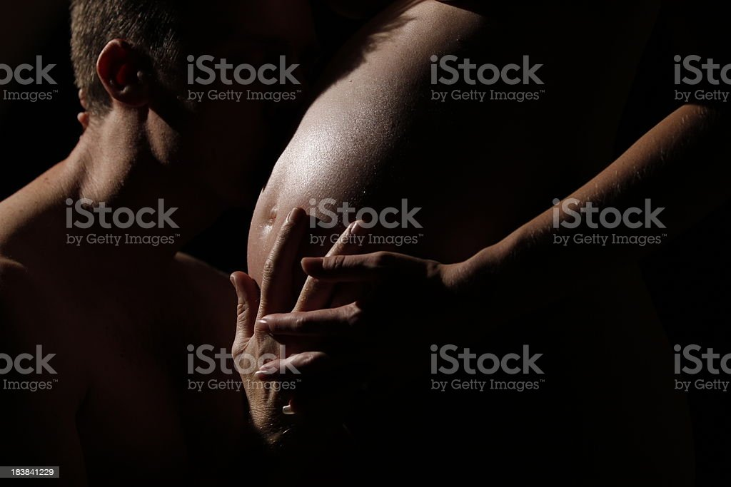 man embraces pregnant belly royalty-free stock photo