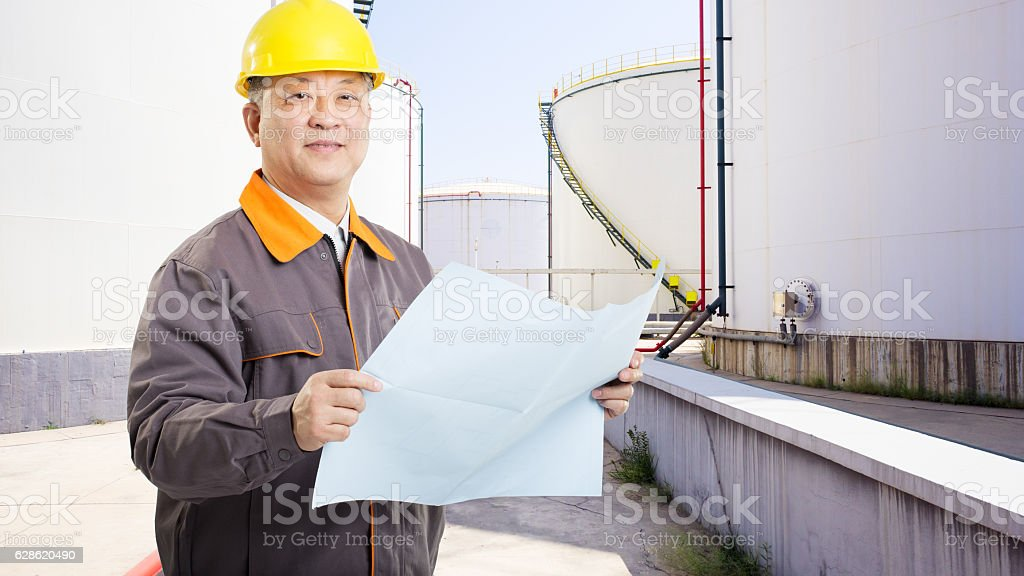 man engineer with helmet and oil tanks stock photo