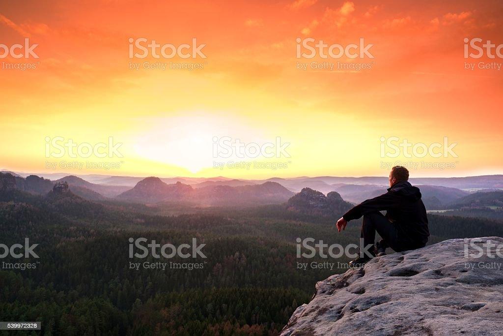 Man enjoing watching orange daybreak in mountains stock photo