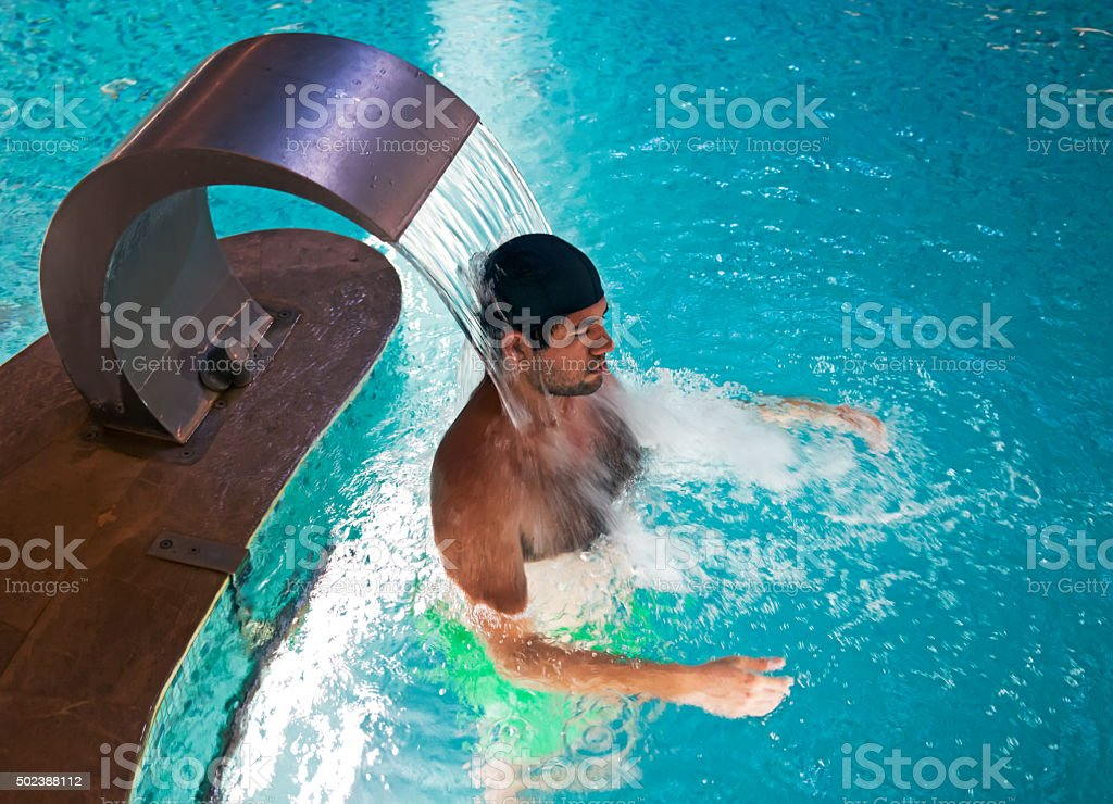 man enjoying a jet of hot thermal water with bonnet stock photo