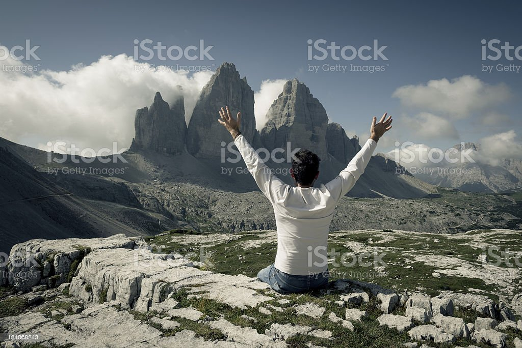 Man enjoying a view from top of the mountain stock photo