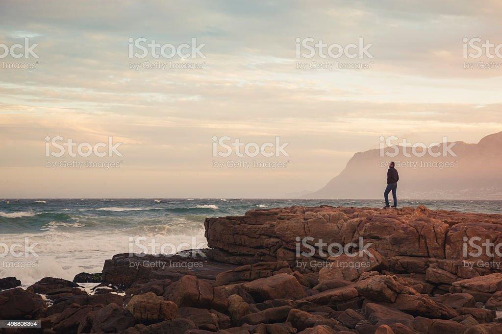 Man enjoying view of wavy ocean during sunset (South Africa) stock photo