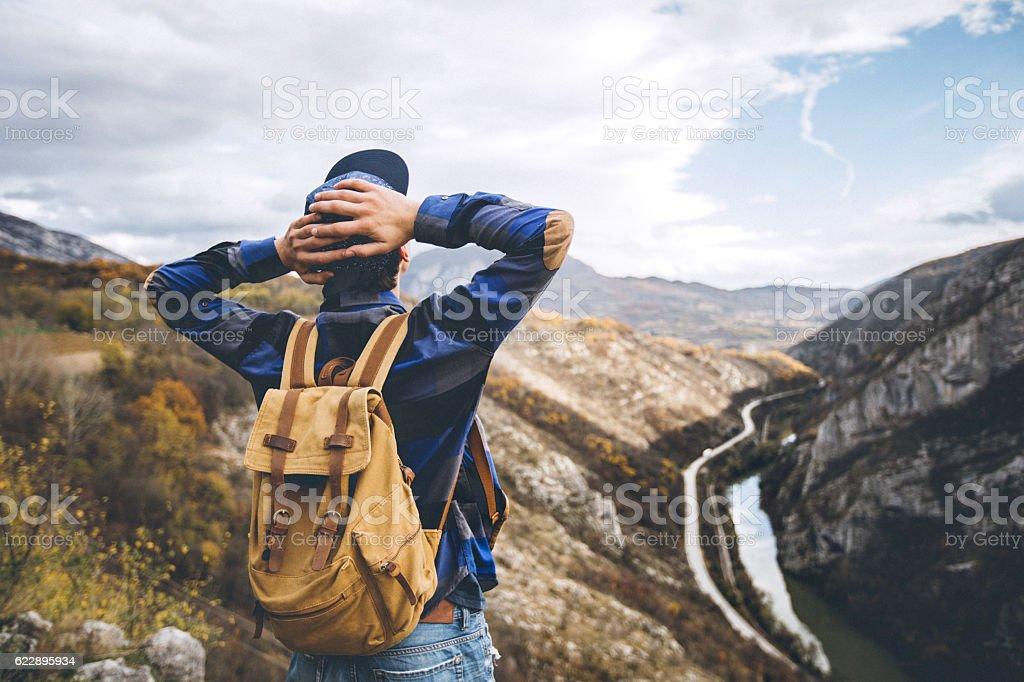 Man enjoys on the mountain and looking to the horizon stock photo