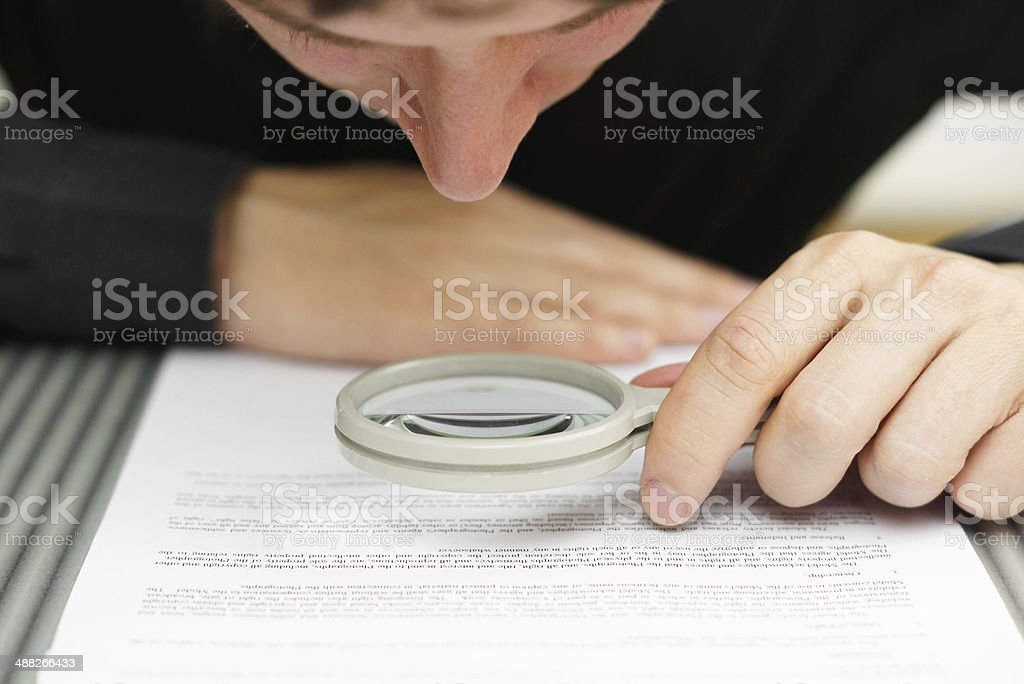 Man examining a document with a magnifying glass stock photo