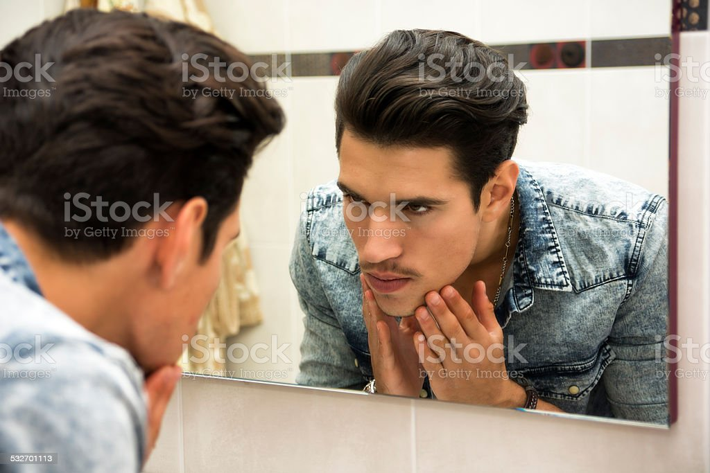 Man Examining Face in Reflection of Mirror stock photo