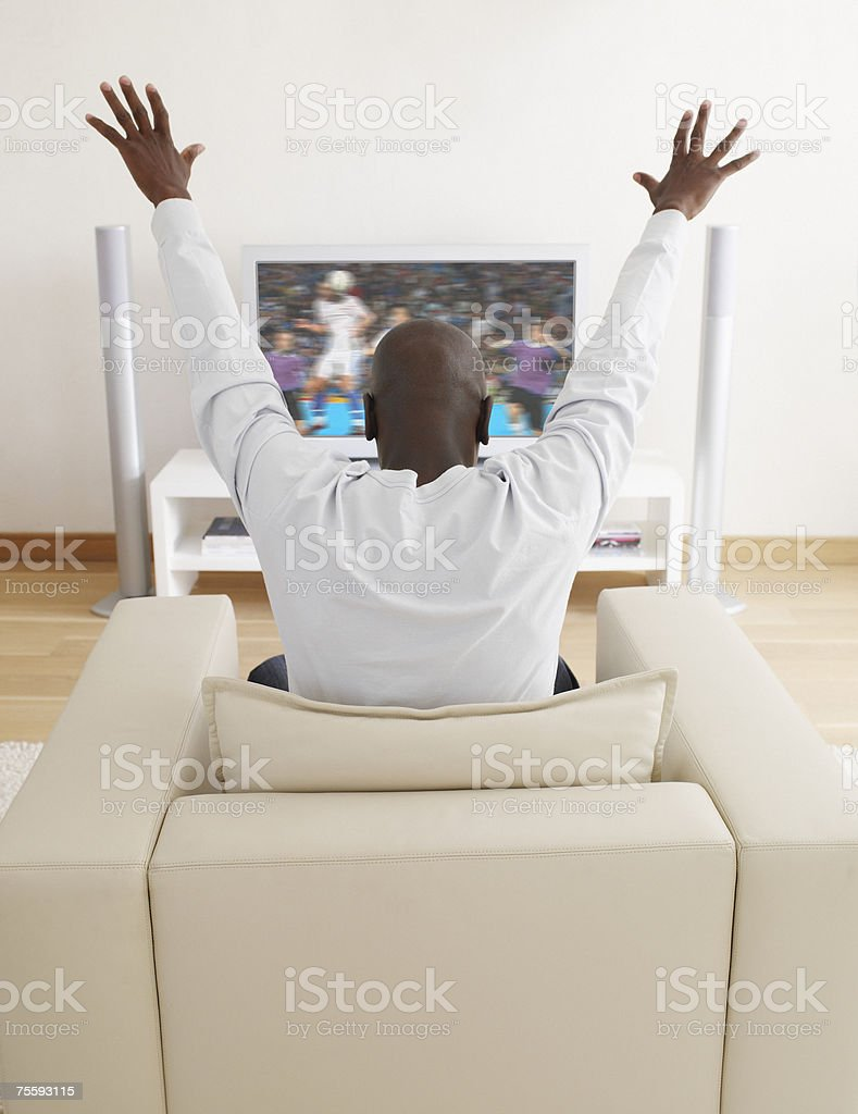 Man excitedly watching television stock photo