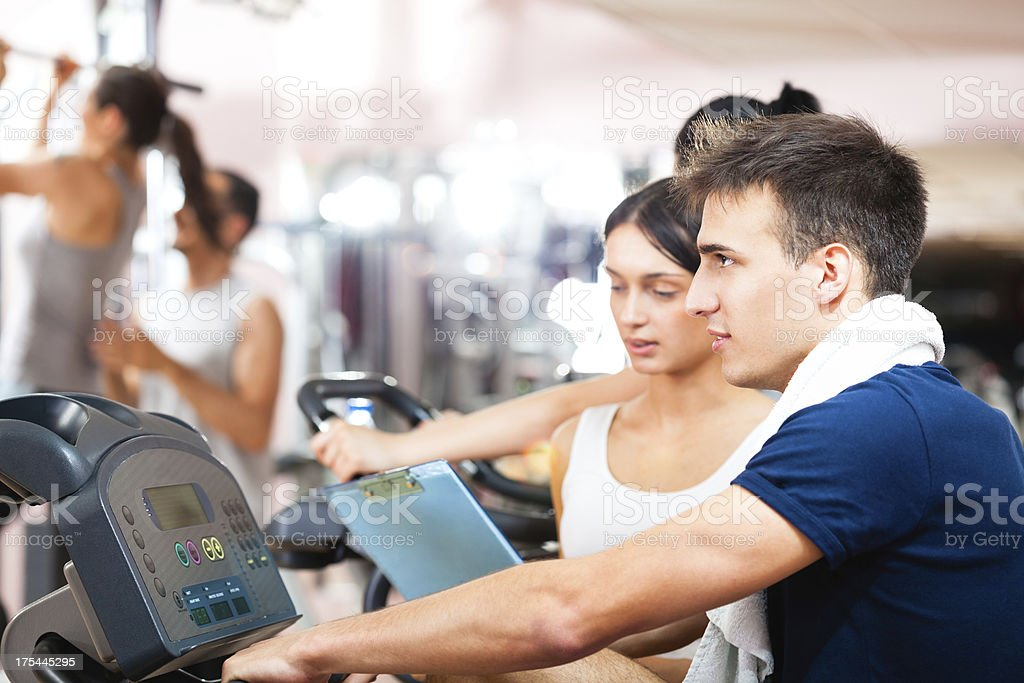 Man spinning in gym with personal fitness instructor stock photo