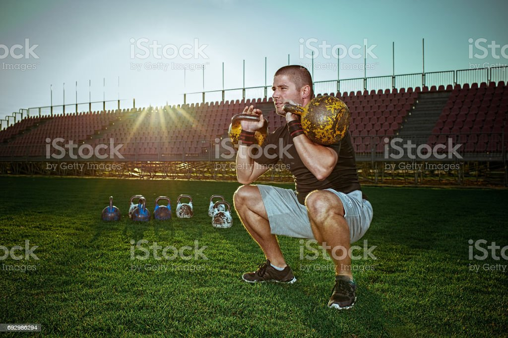 Man exercising with kettlebells outside stock photo