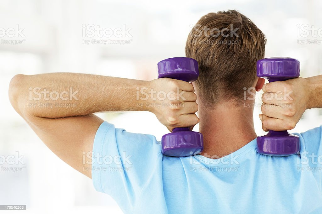 Man Exercising With Purple Weights In Health Club royalty-free stock photo