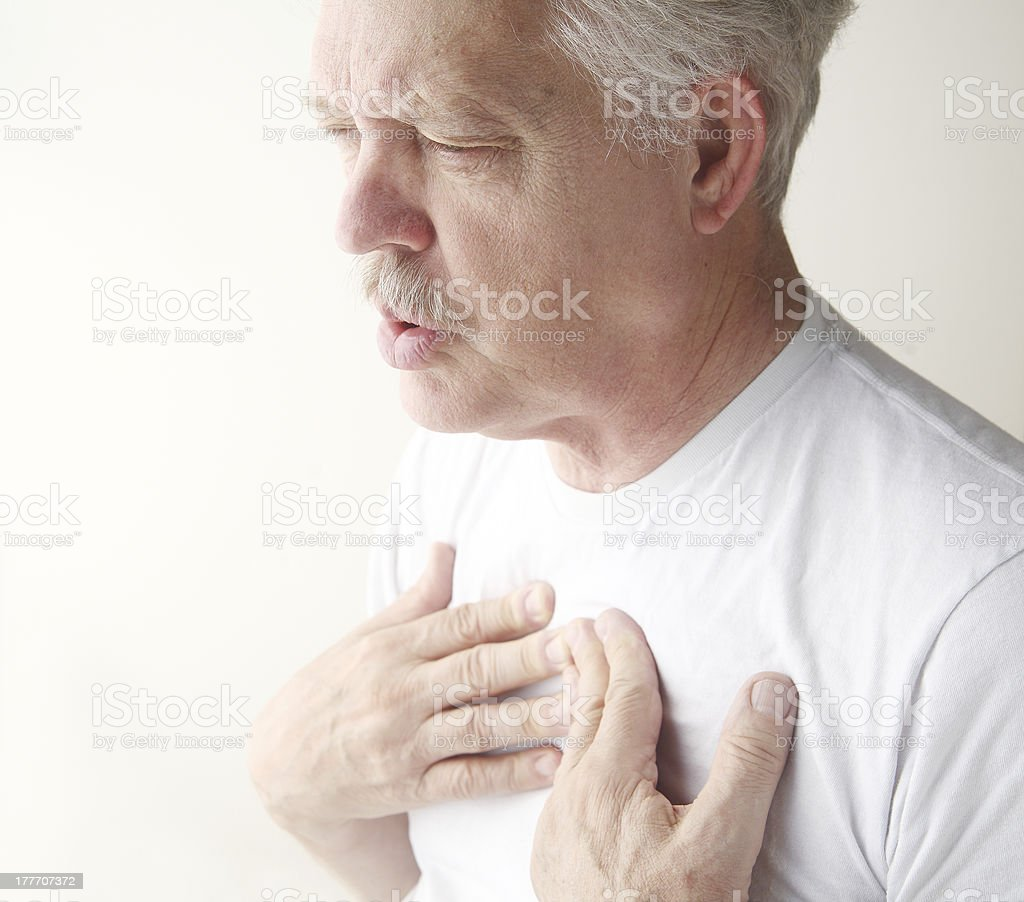 man exhales with hands on chest stock photo