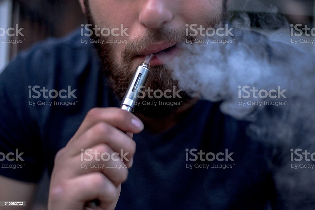 Man Exhaling Vapour from E-Cigarette stock photo