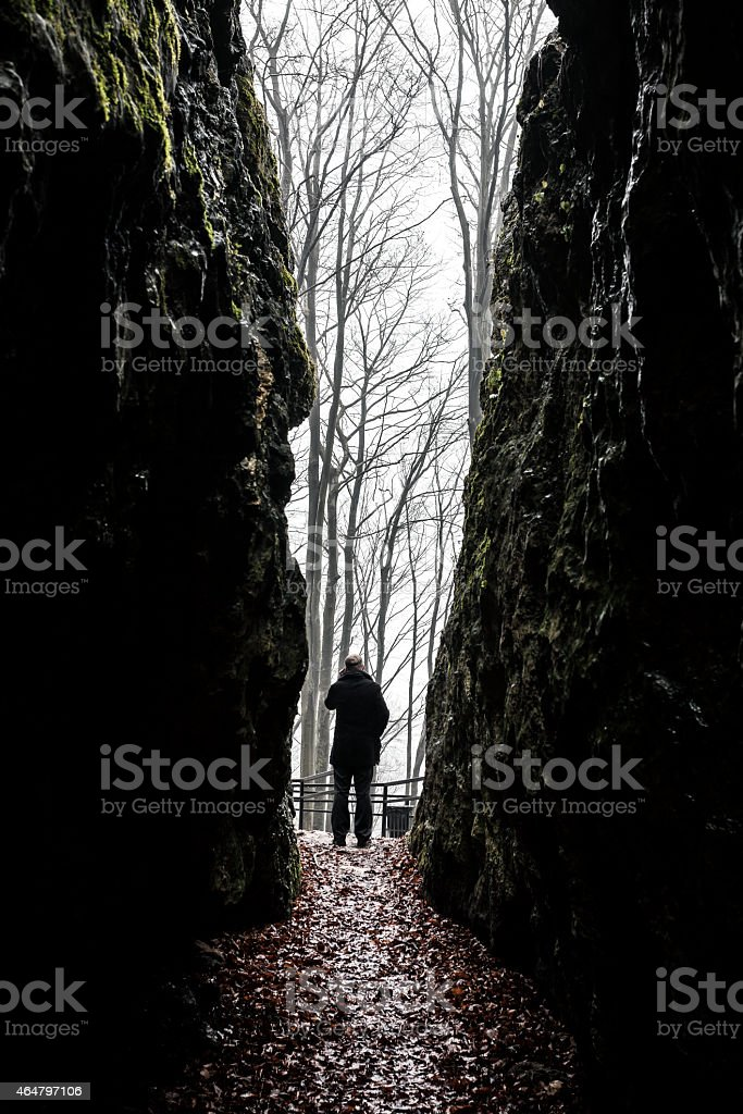 Man exiting dark cave stock photo