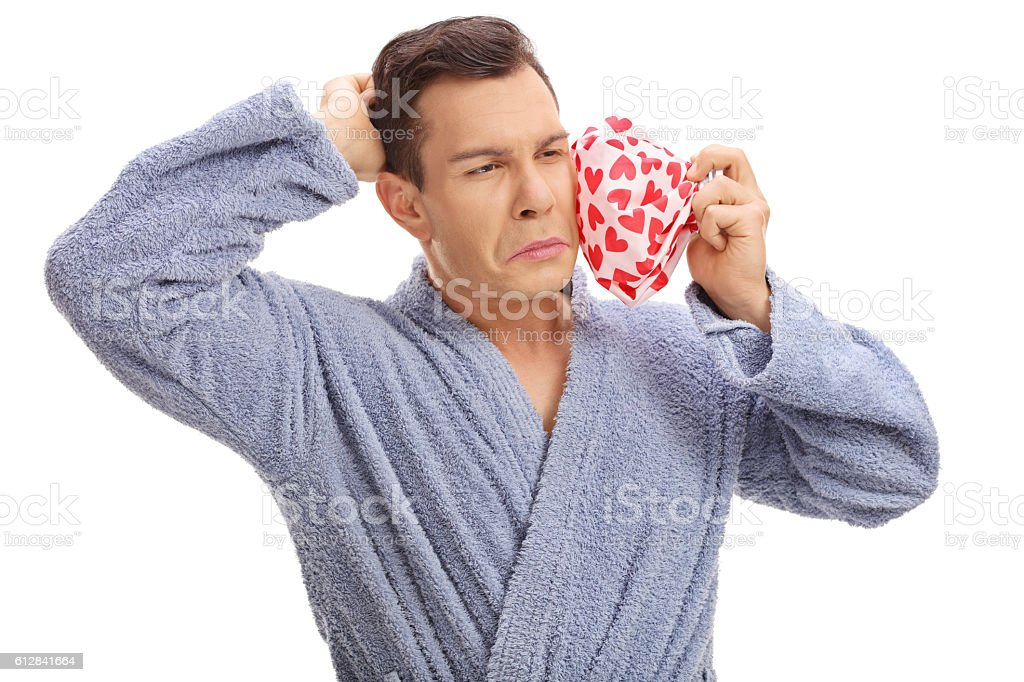 Man experiencing a toothache and holding an icepack stock photo