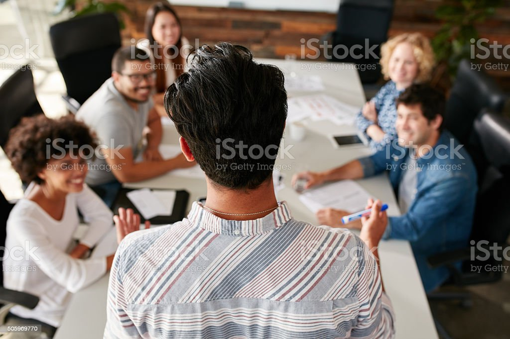 Man explaining business ideas to colleagues stock photo
