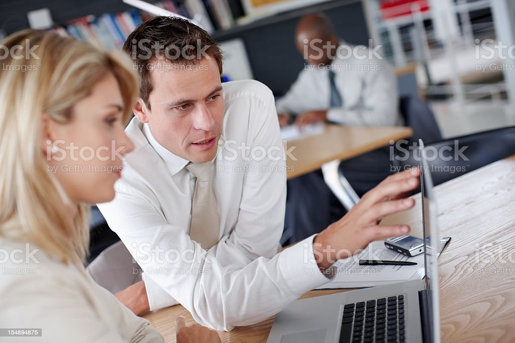 Man explaining business plans to female colleagues on the laptop royalty-free stock photo