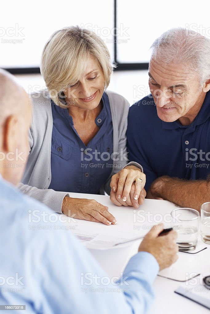 Man explaining investment plans to senior couple stock photo