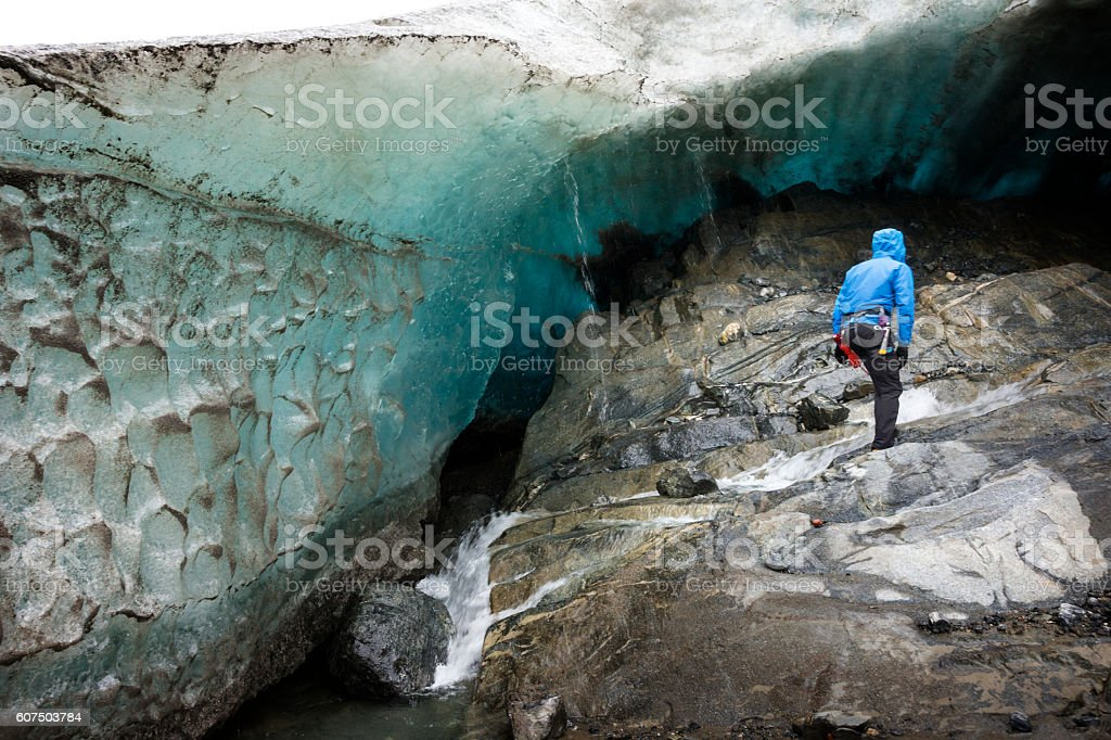 Man explores an ice wall at terminus base of Glacier stock photo