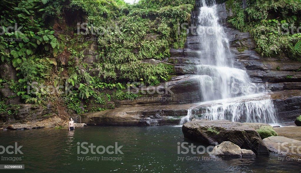 Mann zu idyllischen tropischen Dschungel-Wasserfall des Yaeyama islands Lizenzfreies stock-foto