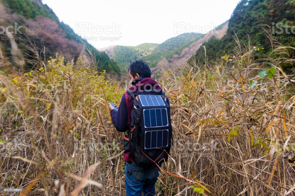 Man exploring thre wilderness with solar powered navigation equipment stock photo