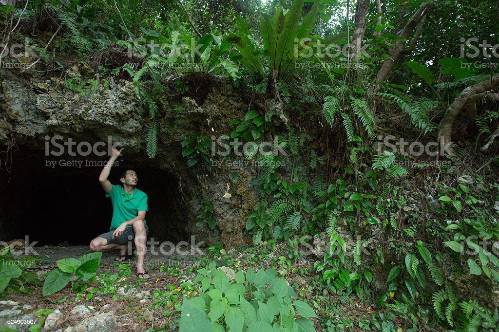 Mann zu tropischen Dschungel-Höhle umgeben von üppiger, grüner vegetation Lizenzfreies stock-foto