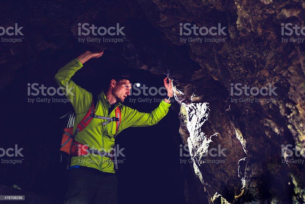 Man exploring underground dark cave tunnel stock photo