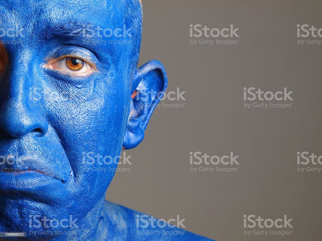 Man face painted with color blue, sad. royalty-free stock photo