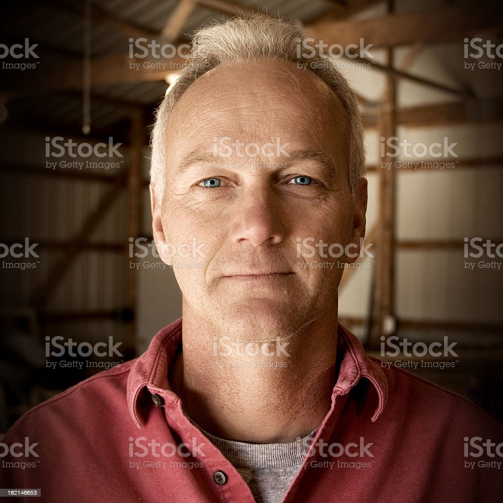 Man facing camera with interior of barn as the background stock photo