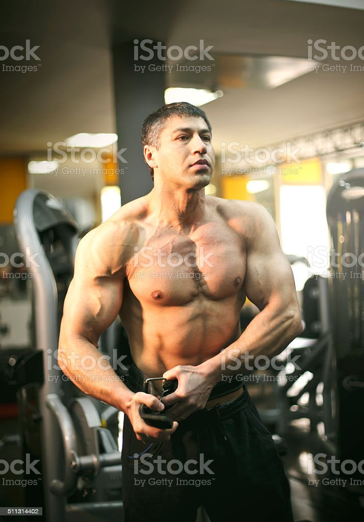 Man fastening belt in the gym stock photo
