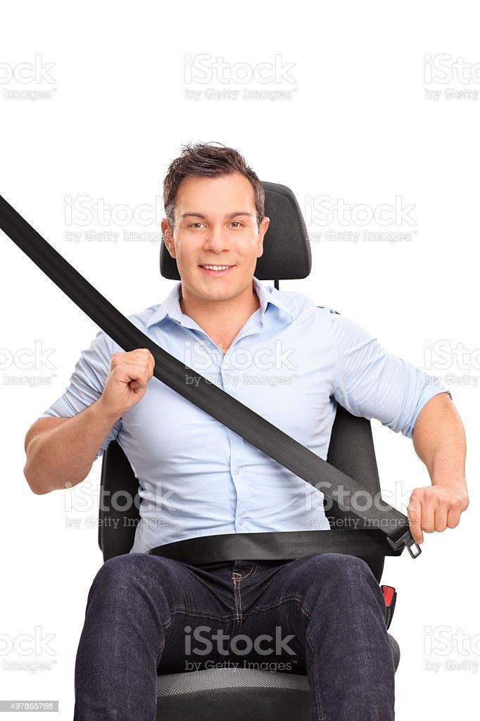 Man fastening his seat belt on a car seat stock photo