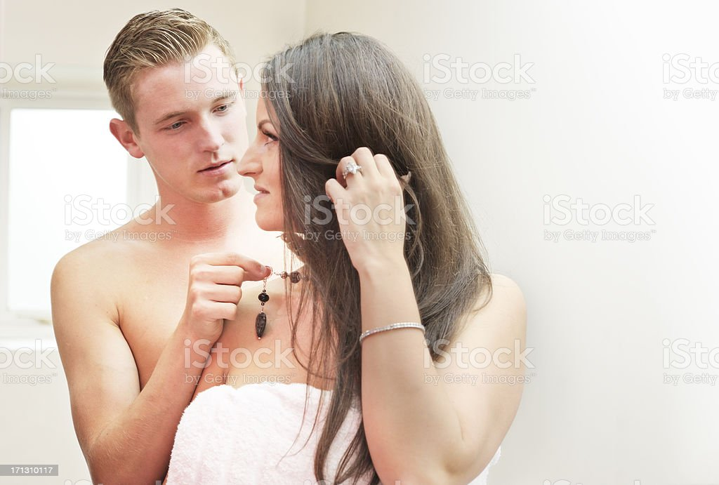 Man fastening woman's necklace in bathroom stock photo