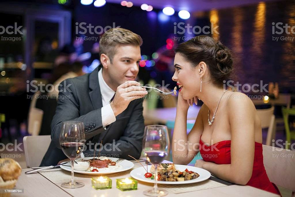 man feeding woman stock photo