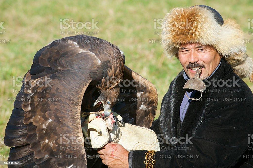 Man feeds golden eagle, circa Almaty, Kazakhstan. stock photo